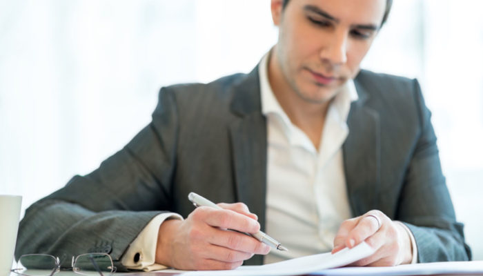 Handsome businessman analysing a report making notes with his pen on the paperwork, close up facing camera.